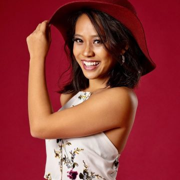 headshot of Kaley smiling and wearing a red fashion hat