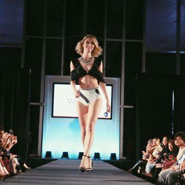 Megan on the runway wearing a classy black and white bikini and black heels
