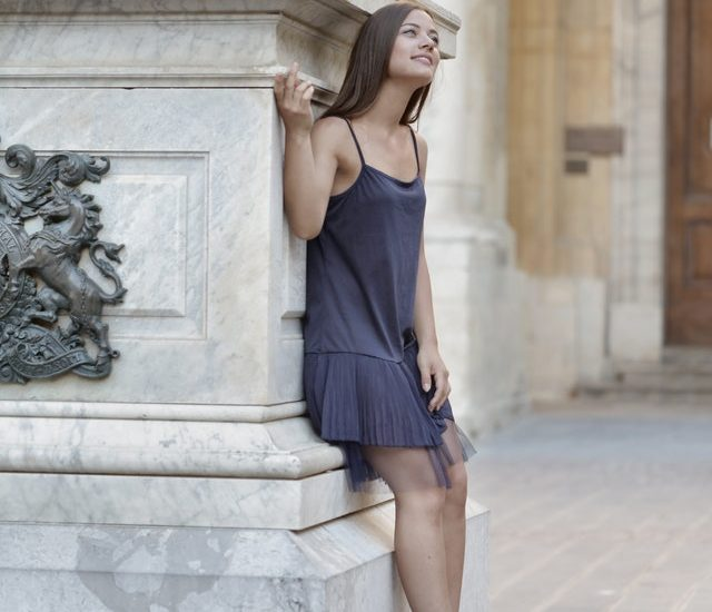 Girl leaning against a monument posing for a photo